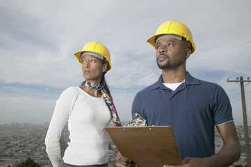 African man and woman with hard hats and clipboard