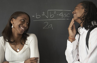 Two African students next to math problem on blackboard