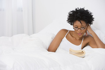Young African woman reading in bed