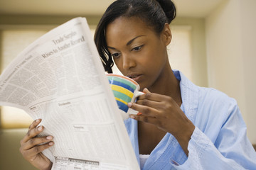 African woman reading newspaper and drinking coffee indoors