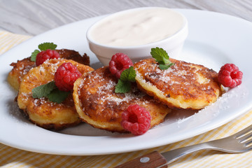 Cheese pancakes with raspberries and sour cream horizontal
