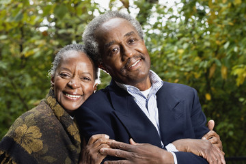 Senior African couple smiling in woods