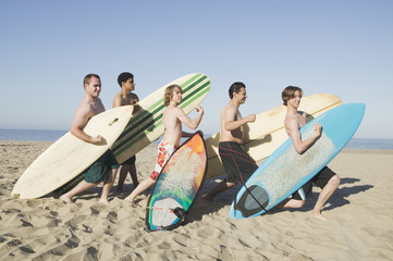 Multi-ethnic surfers holding surfboards and flexing on beach