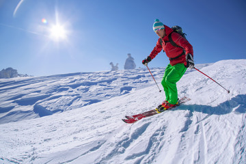 Skier against blue sky in high mountains