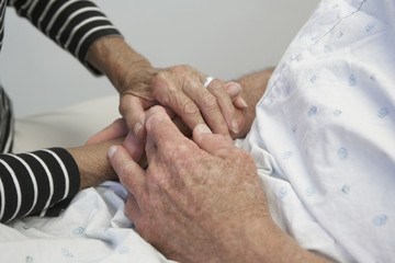 Close up of senior couple holding hands in hospital