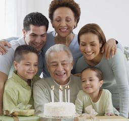 Senior Hispanic man celebrating birthday with family