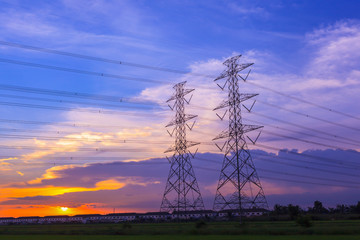 high voltage post tower and power line on sunset sky background