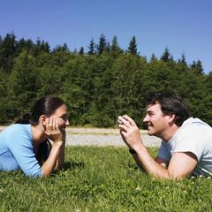 Man taking photograph of girlfriend in grass