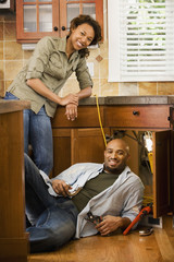 African couple installing kitchen sink