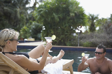 Couple having cocktails at swimming pool