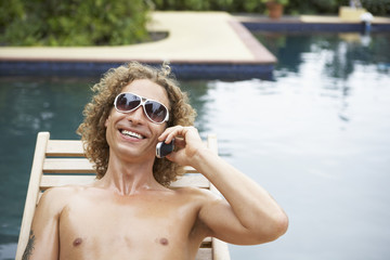Man talking on cell phone next to swimming pool