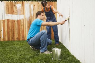 Multi-ethnic couple painting fence