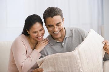 Hispanic couple reading newspaper
