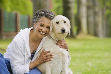 African American woman hugging dog