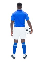 Football player in blue standing with the ball