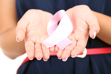 Woman with aids awareness pink ribbon in hands isolated on