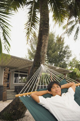 Asian man laying in hammock