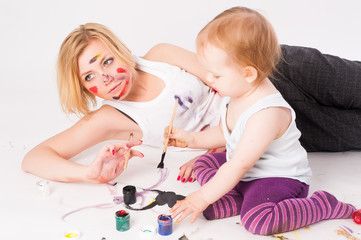 Pretty young mother and daughter drawing