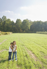 Hispanic sisters hugging in field