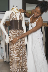 African woman adjusting dress on mannequin