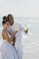 Multi-ethnic couple drinking wine at beach