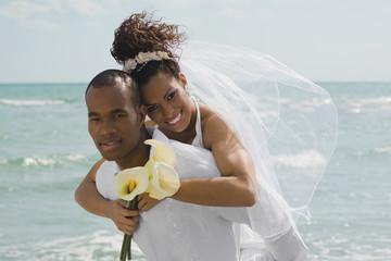 Multi-ethnic bride and groom hugging at beach