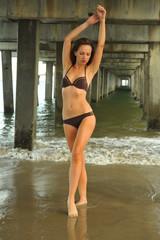 Beautiful bikini model posing pretty under the pier.