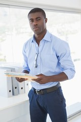 Serious businessman holding documents looking at camera