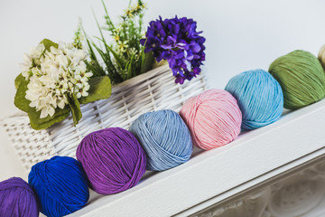 Collection of colorful balls of woolen yarn on the shelf