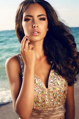 beautiful girl with dark hair in luxurious dress posing on beach