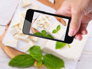 Hands taking photo  feta with smartphone