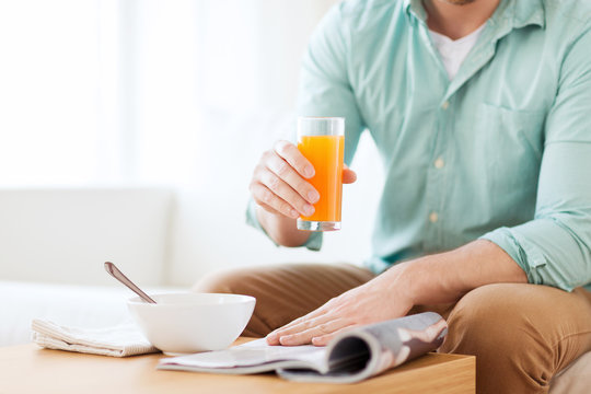 close up of man with magazine drinking juice
