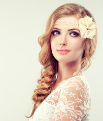 Beautiful model in lace dress with a pigtail , flower barrette