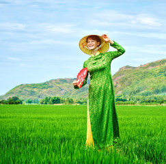 Girl in national Vietnamese dress is waving happily with veeк