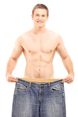 Shirtless weightloss male showing his old pair of jeans