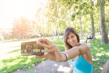 Beautiful Young Woman Taking Selfie at Park