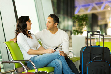 young couple waiting for their flight at airport