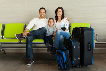 family with luggage waiting at airport