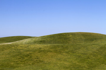 Photo sur Aluminium Colline View of bare green hills with a blue sky.