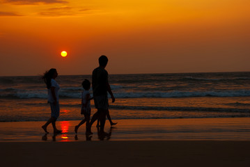 silhouette of family walking along the coast at the sunset