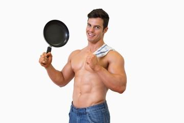 Portrait of a shirtless muscular man holding frying pan