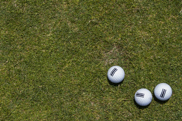 three golf balls on a corner in a green grass