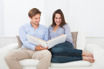 Couple Looking At Their Photo Album On Sofa