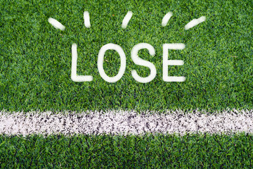 LOSE hand writing text on soccer field grass