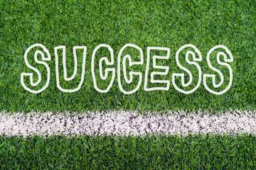 SUCCESS hand writing text on soccer field grass