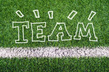 TEAM hand writing text on soccer field grass