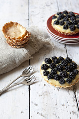 two homemade blackberries tart with pastry cream on wooden table