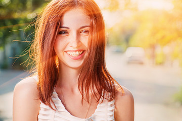 Smiling redhead outdoors backlit by sun , shot with flares