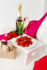 Romantic still life with champagne, strawberry and roses on