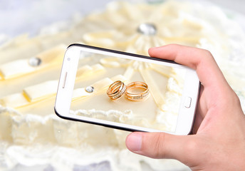 Hands taking photo wedding rings with smartphone